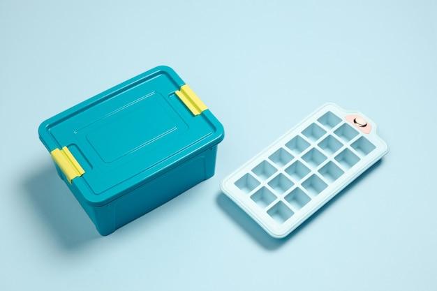 閉じたお弁当箱、氷の形。スタジオの壁に青い色のモノクロのスタイリッシュでトレンディな構成。上面図、フラットレイ。