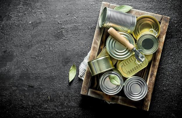 오프너와 함께 쟁반에 통조림 식품이 담긴 닫힌 금속 캔. 검은 소박한 표면에