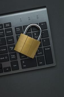 Закрытый металлический замок на клавиатуре компьютера на темном столе. понятие компьютерной безопасности. плоская планировка.