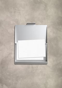 Закрытая металлическая визитница, изолированная на бетонном столе