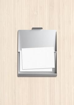 Закрытая металлическая визитница изолирована на белом деревянном фоне