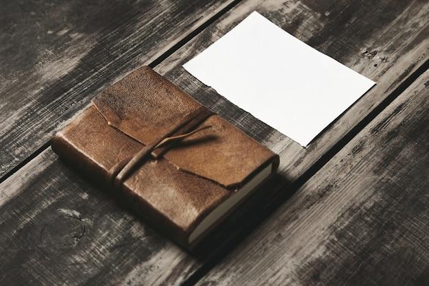 黒い農場のビンテージブラシをかけられた木製のテーブルの上の白い紙のシートの近くのgeniune革カバーの閉じたノートブック