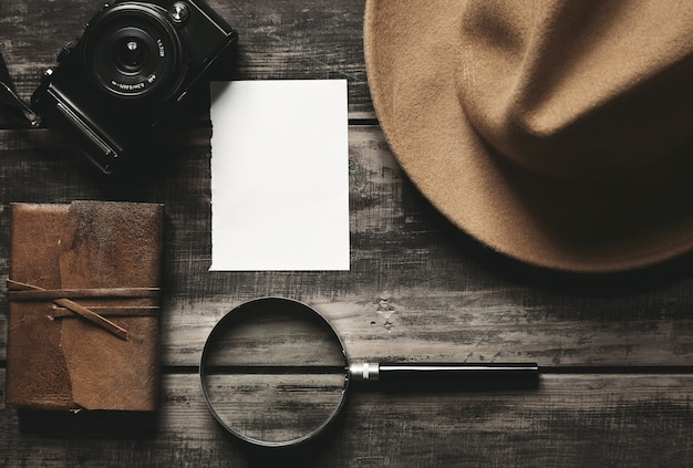 Closed notebook in leather cover, sheet of white paper, felt brown hat, camera and big magnifier isolated on black aged wood table