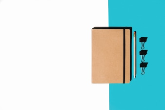 Closed notebook with brown cover; pencil and bulldog clips on white and blue background
