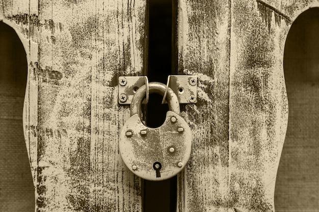 나무로 되는 문 경첩에 걸려 있는 닫힌 오래된 금속 자물쇠