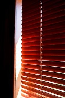 Закрытые оранжевые пластиковые жалюзи с солнечным светом по утрам. окно с жалюзи. дизайн интерьера гостиной с оконными горизонтальными жалюзи. окно с солнцезащитными жалюзи