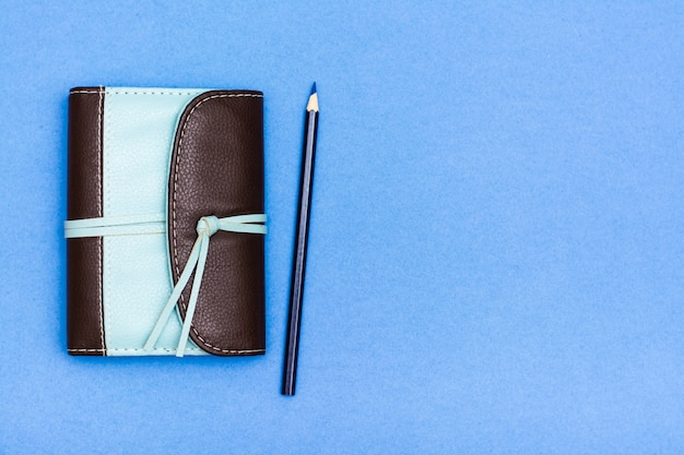 Closed organizer in a two-color leather binding and a pencil on a blue background