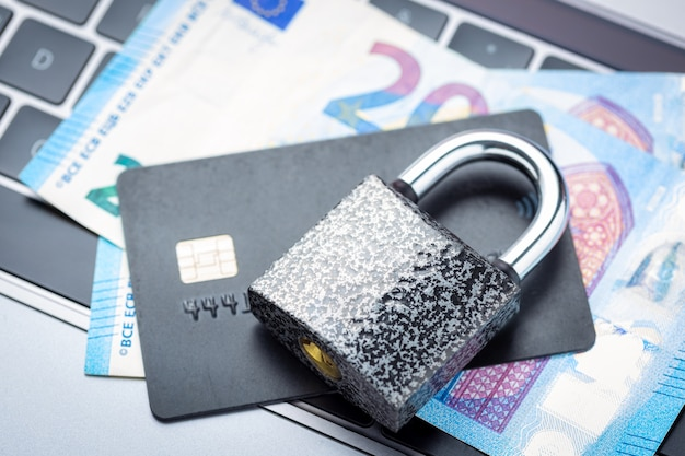 Закрытый замок с деньгами и кредитной картой на клавиатуре ноутбука