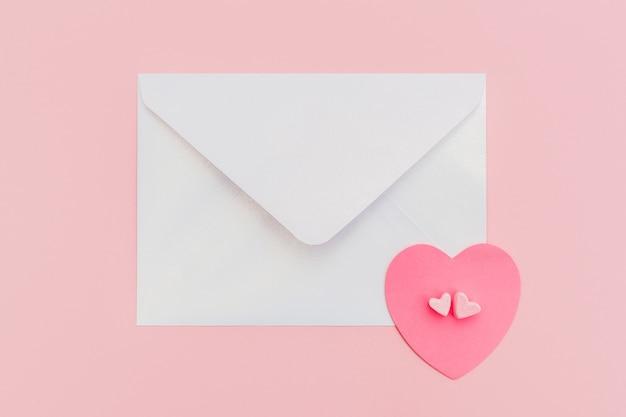 ピンクの背景に紙のハートと閉じた真珠光沢のある封筒