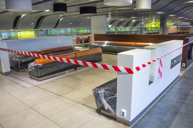 Closed places of a public catering tables and seats for people are fenced with a restrictive tape. coronavirus, covid 19 pandemic, quarantine concept.