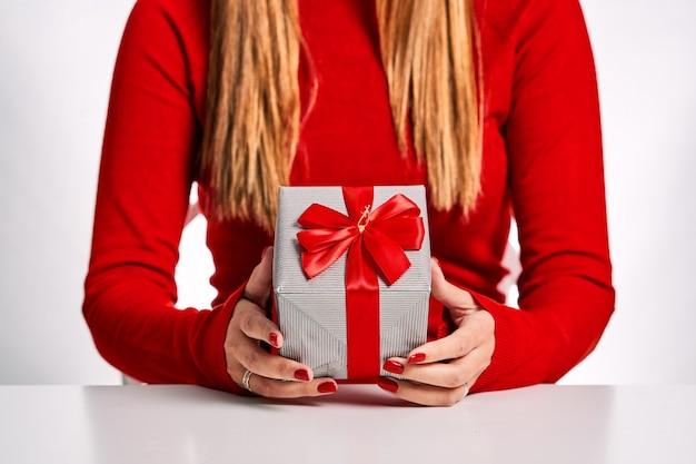 赤いセーターと白い背景で隔離の彼女の手にギフトボックスを持つ女性のクローズドプラン。