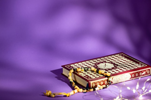 Closed quran on purple background