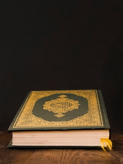 Closed quran on a table with black background
