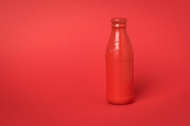 A closed red bottle on a bright red background. a container for refreshing drinks.