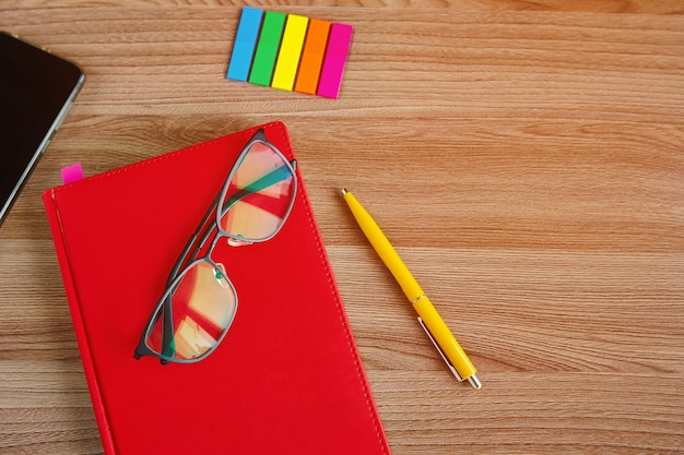 Closed red notepad, glasses on a wooden background, top view
