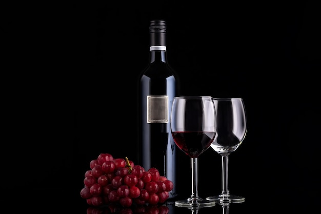 Closed red wine bottle with empty label, small branch of grape and two glasses on black background with reflections