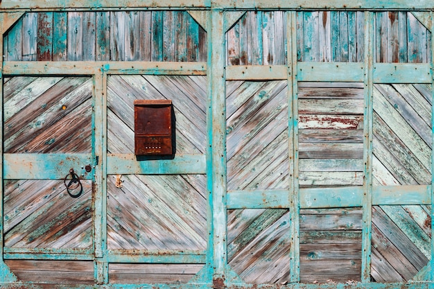 Closed rustic imperfect green garage gate with turquoise peeling paint close-up.