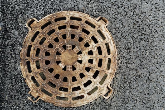 Закрытый канализационный люк, который находится на тротуаре, в крышке люка имеются отверстия Premium Фотографии