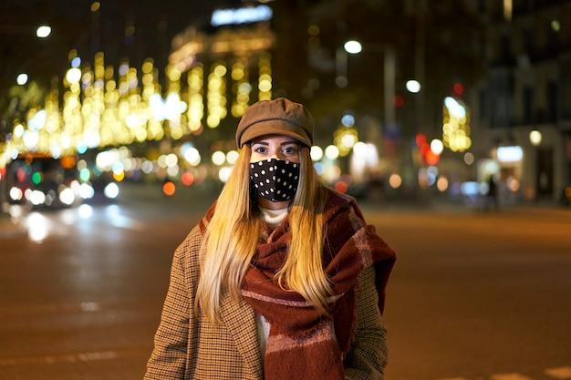 Закрытый снимок молодой блондинки в маске, стоящей перед камерой, в ночном городе с множеством фоновых огней и проезжающими автомобилями. зимняя атмосфера.