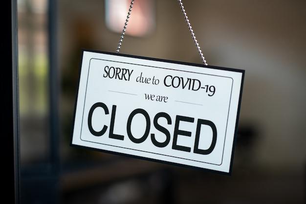 Covid-19のためにカフェのドアに掛かっている閉じた看板
