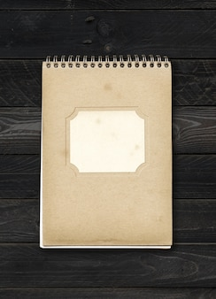 Closed spiral note book with empty label on a black wood table. mockup