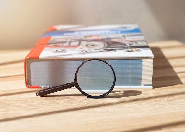나무 책상에 돋보기가 있는 닫힌 기술 책을 닫습니다.