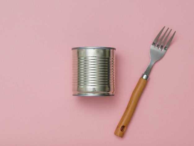 ピンクの背景に閉じたブリキ缶とフォーク。缶詰用のユニバーサルコンテナ。