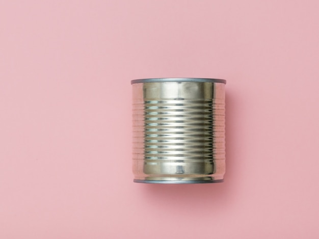 Closed tin can and fork on a pink background. universal container for canning.