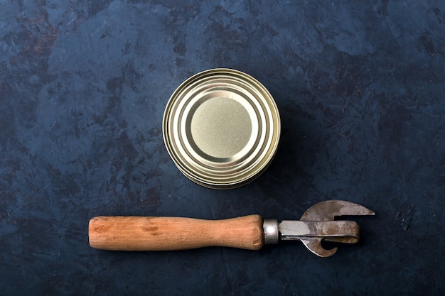 濃い青色の背景に栓抜き付きの閉じたブリキ缶、テキスト用のスペース