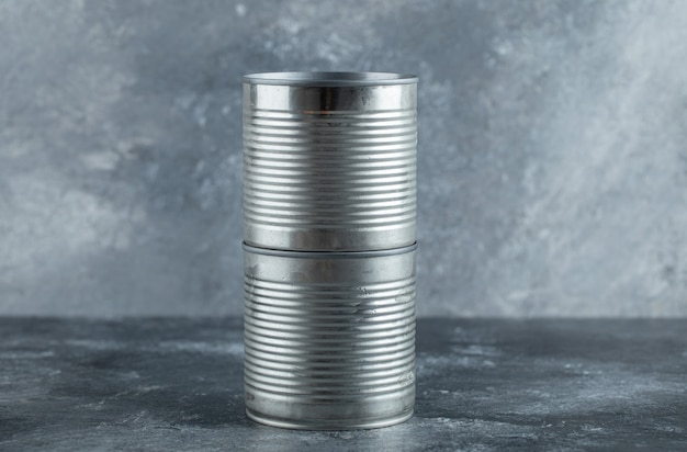 Closed tin cans placed on marble.