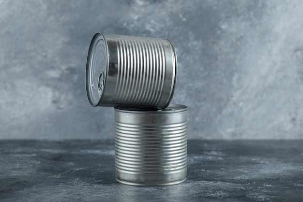 Closed tin cans with vegetables placed on marble.