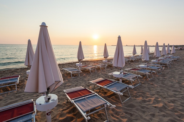 閉じた傘と美しい夕日の椅子。
