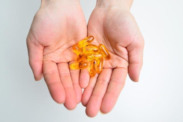 Закрытые большие таблетки желатиновых капсул рыбьего жира в руке, изолированные на белом фоне