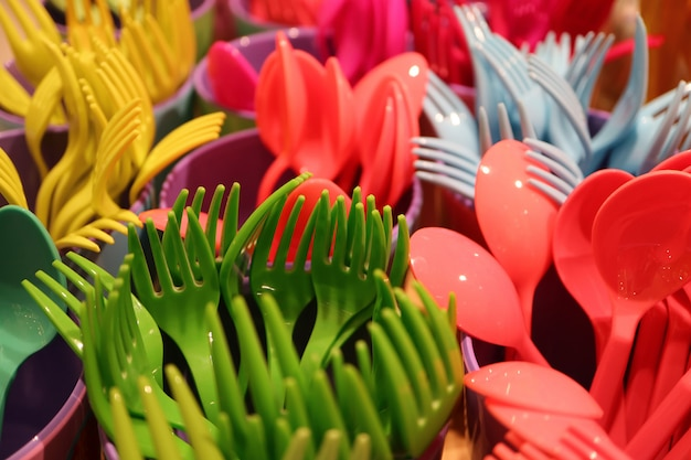 Closed up bunch of multi-color plastic ware cutlery with selective focus