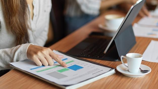 Закрыл бизнесвумен, глядя на финансовые документы с ноутбуком на офисном столе