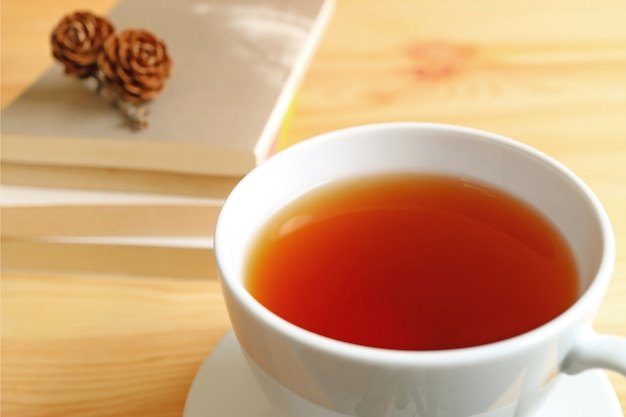 Closed up a cup of hot tea on wooden table with blurred stack of books and dry pine cones
