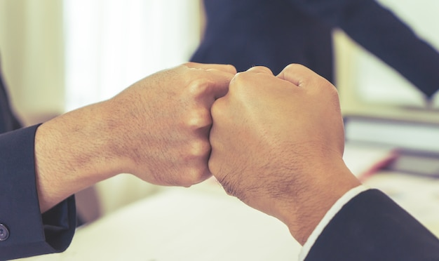 Closed up fist bump in business meeting for team concept