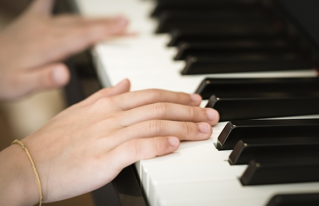 Closed up hand hand playing music piano keyboard, side view.