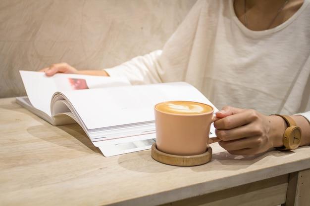 Закрытые руки с чашкой латте арт-кофе и открытие журнала или книги.