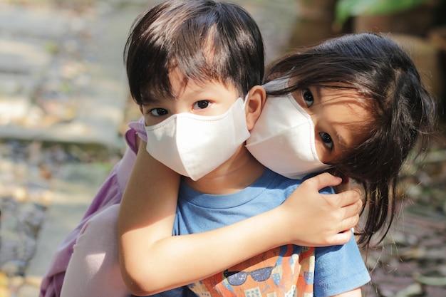コロナウイルス防止のためのマスクを身に着けている子供のヘッドショットをクローズアップ