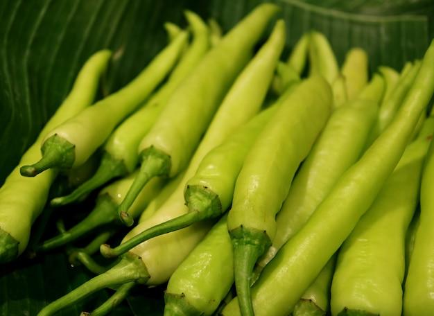 Closed up heap of bright green fresh capsicum on banana leaf