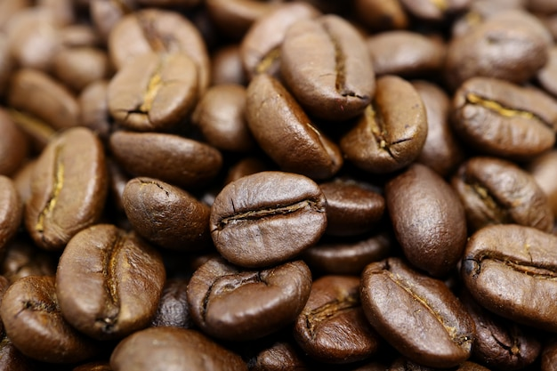 Closed up heap of roasted coffee beans with selective focus and blurred background