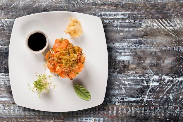 Закрытые тарелки салата с кусочками сырого лосося.