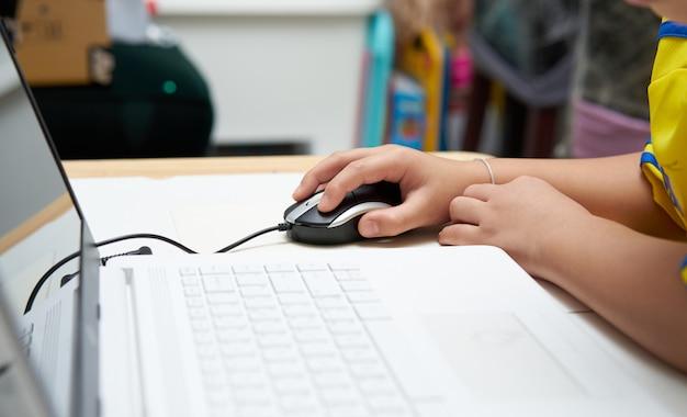 子供の手とノートとマウスのクローズアップ