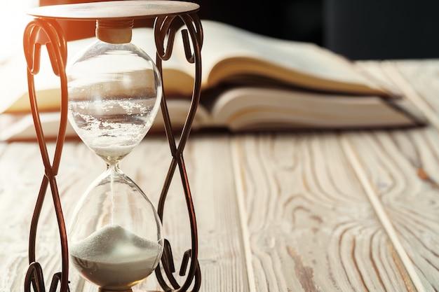 本の背景に砂時計または砂時計のクローズアップ