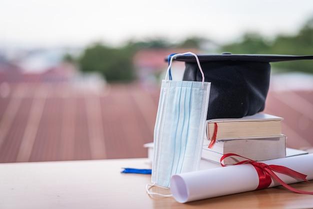 Закрытое фото ступки кепки окончания колледжа с аттестатом диплома и лицевой маской на столе. выпускной в эпоху covid-19
