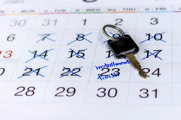 Закрытое изображение ключа от машины на белом календаре с отмеченной датой, чтобы отметить напоминание о назначении платежа в рассрочку для финансирования автомобиля.