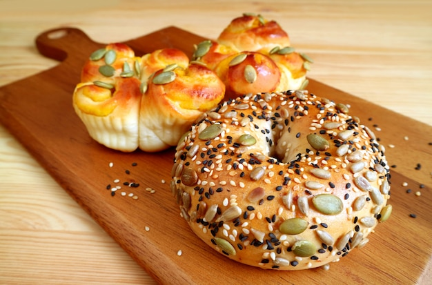 Closed up pumpkin deeds and sesame buns on the wooden tray