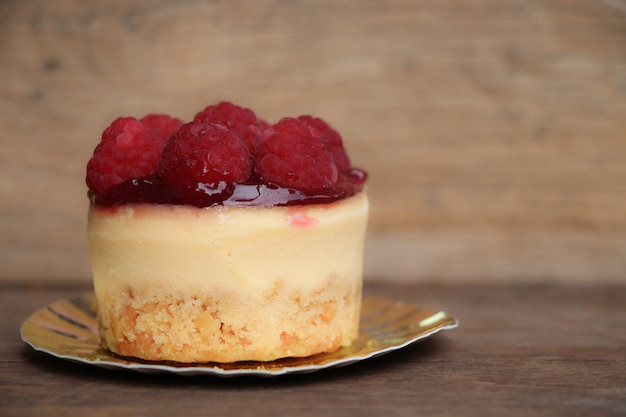 Closed up raspberry cheese cake sweet bake and beautiful topping of  fruit on wood background