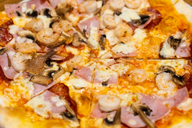 Closed up of seafood pizza on wooden table.